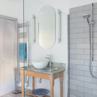 This is an example of a medium sized traditional shower room bathroom in London with freestanding cabinets, a corner shower, grey tiles, porcelain tiles, white walls, porcelain flooring, a vessel sink, grey floors, an open shower, green worktops, a single sink and a freestanding vanity unit.