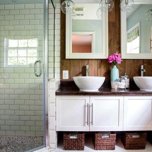 Imagen de cuarto de baño principal, ecléctico, de tamaño medio, con lavabo sobreencimera, armarios estilo shaker, puertas de armario blancas, encimera de cemento, ducha esquinera, baldosas y/o azulejos blancos, baldosas y/o azulejos de cemento, paredes verdes y suelo de baldosas de porcelana