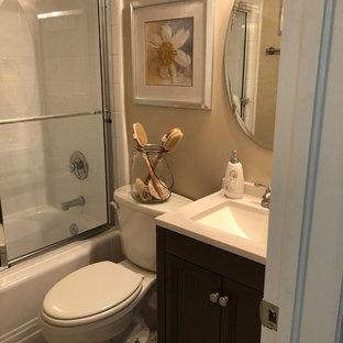 Esempio di una piccola stanza da bagno stile marino con ante in stile shaker, ante grigie, vasca ad alcova, doccia alcova, WC a due pezzi, pareti beige, pavimento in vinile, lavabo integrato, top in superficie solida, pavimento beige, porta doccia scorrevole e top bianco