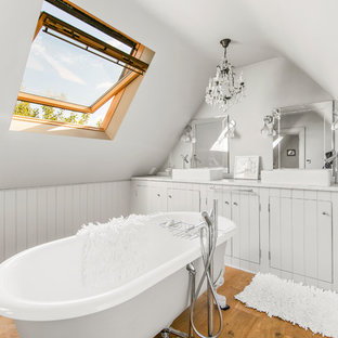 Photo of a classic ensuite bathroom in London with grey cabinets, a claw-foot bath, grey walls, light hardwood flooring, a vessel sink and white worktops.