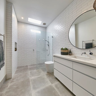 Design ideas for a 3/4 bathroom in Perth with flat-panel cabinets, white cabinets, a curbless shower, a one-piece toilet, white tile, white walls, an undermount sink, grey floor, an open shower and white benchtops.