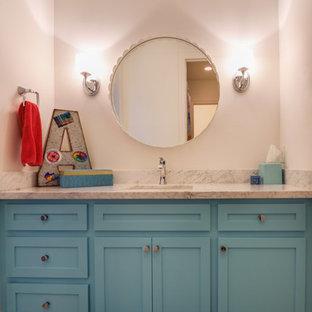 Immagine di una stanza da bagno per bambini tradizionale di medie dimensioni con lavabo sottopiano, ante con riquadro incassato, ante blu, top in marmo, vasca/doccia, piastrelle grigie, piastrelle in gres porcellanato, pareti bianche e pavimento in gres porcellanato
