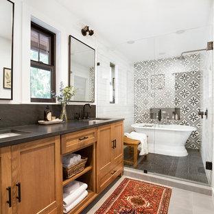 Неиссякаемый источник вдохновения для домашнего уюта: главная ванная комната в стиле кантри с фасадами в стиле шейкер, фасадами цвета дерева среднего тона, отдельно стоящей ванной, душевой комнатой, черно-белой плиткой, белыми стенами, врезной раковиной, серым полом, душем с распашными дверями и черной столешницей