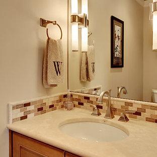 Diseño de cuarto de baño clásico renovado, de tamaño medio, con armarios con rebordes decorativos, puertas de armario de madera oscura, baldosas y/o azulejos beige, baldosas y/o azulejos en mosaico, paredes beige, suelo de bambú, lavabo bajoencimera y encimera de piedra caliza