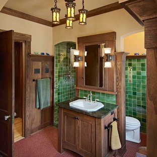 Example of an arts and crafts green tile red floor bathroom design in Minneapolis with a drop-in sink, dark wood cabinets, shaker cabinets and green countertops