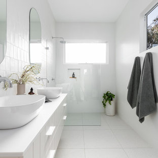 Inspiration for a beach style bathroom in Sydney with flat-panel cabinets, white cabinets, a curbless shower, white tile, a vessel sink, white floor, an open shower, white benchtops, a niche and a double vanity.