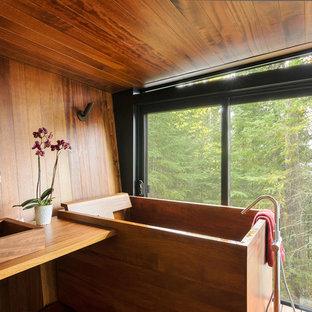 Diseño de cuarto de baño principal, rural, con bañera japonesa, lavabo sobreencimera y encimera de madera