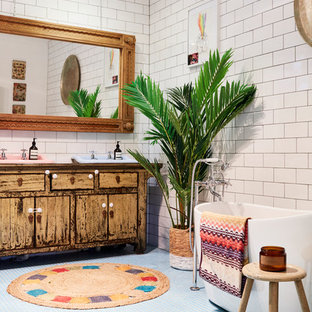Design ideas for an eclectic master bathroom in Gold Coast - Tweed with distressed cabinets, subway tile, furniture-like cabinets, a freestanding tub, white walls, mosaic tile floors and a drop-in sink.