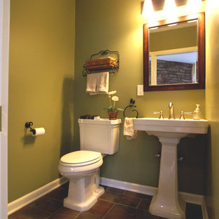 This is an example of a mid-sized traditional 3/4 bathroom in New York with a one-piece toilet, green walls, ceramic floors, a pedestal sink and solid surface benchtops.