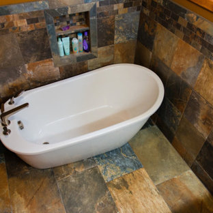 Freestanding bathtub - mid-sized traditional master beige tile, black tile, brown tile, gray tile and stone tile slate floor and multicolored floor freestanding bathtub idea in Other with brown walls