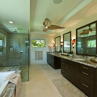 Foto di una grande stanza da bagno padronale tropicale con lavabo sottopiano, ante lisce, ante in legno bruno, top in granito, vasca da incasso, doccia ad angolo, pareti verdi, pavimento in travertino, piastrelle grigie, pavimento beige e porta doccia a battente