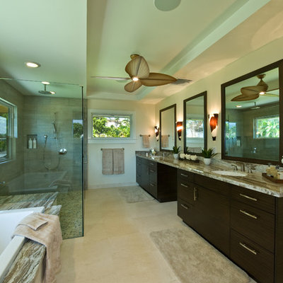 Inspiration for a large tropical master gray tile travertine floor and beige floor bathroom remodel in Hawaii with an undermount sink, flat-panel cabinets, dark wood cabinets, granite countertops, green walls and a hinged shower door