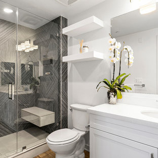 Inspiration for a mid-sized transitional 3/4 gray tile and porcelain tile brown floor alcove shower remodel in Los Angeles with white walls, shaker cabinets, white cabinets, an undermount sink, a hinged shower door and white countertops