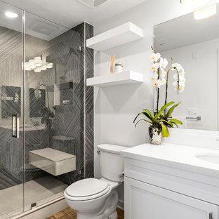 Immagine di una stanza da bagno con doccia classica di medie dimensioni con piastrelle grigie, piastrelle in gres porcellanato, pareti bianche, ante in stile shaker, ante bianche, doccia alcova, lavabo sottopiano, pavimento marrone, porta doccia a battente e top bianco