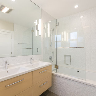 Inspiration for a mid-sized modern white tile, gray tile and mosaic tile tub/shower combo remodel in San Francisco with an integrated sink, flat-panel cabinets, solid surface countertops, an undermount tub, white walls, light wood cabinets and a hinged shower door