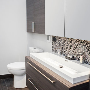 Ejemplo de cuarto de baño actual, pequeño, con lavabo encastrado, armarios con paneles lisos, puertas de armario de madera en tonos medios, encimera de laminado, bañera empotrada, ducha esquinera, sanitario de una pieza, baldosas y/o azulejos blancas y negros, baldosas y/o azulejos en mosaico, paredes grises y suelo de baldosas de cerámica