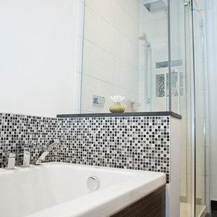Modelo de cuarto de baño actual, pequeño, con lavabo encastrado, armarios con paneles lisos, puertas de armario de madera en tonos medios, encimera de laminado, bañera empotrada, ducha esquinera, sanitario de una pieza, baldosas y/o azulejos blancas y negros, baldosas y/o azulejos en mosaico, paredes grises y suelo de baldosas de cerámica