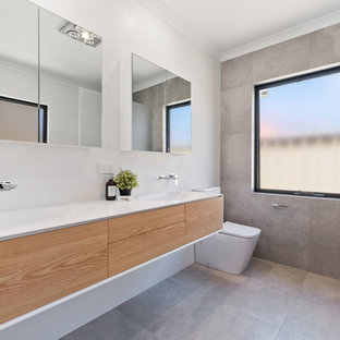 This is an example of a contemporary 3/4 bathroom in Perth with flat-panel cabinets, medium wood cabinets, gray tile, white walls, an integrated sink, grey floor and white benchtops.
