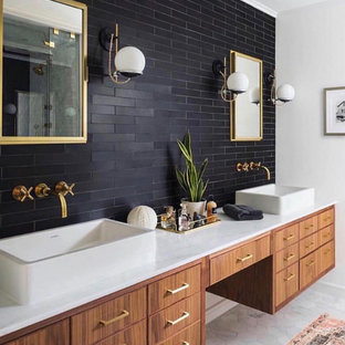 This is an example of a contemporary master bathroom in DC Metro with flat-panel cabinets, medium wood cabinets, black tile, brown walls, a vessel sink, grey floor and white benchtops.
