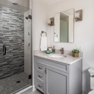На фото: маленькая главная ванная комната в стиле неоклассика (современная классика) с серыми фасадами, душем в нише, раздельным унитазом, разноцветной плиткой, стеклянной плиткой, серыми стенами, врезной раковиной, столешницей из искусственного кварца, серым полом, душем с распашными дверями, белой столешницей, тумбой под одну раковину, встроенной тумбой и фасадами с утопленной филенкой с