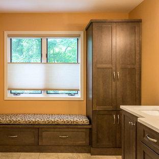 Пример оригинального дизайна интерьера: главная ванная комната среднего размера в стиле кантри с фасадами в стиле шейкер, фасадами цвета дерева среднего тона, полом из керамической плитки, душем в нише, бежевой плиткой, керамической плиткой, оранжевыми стенами, подвесной раковиной, столешницей из искусственного кварца, коричневым полом, душем с распашными дверями и белой столешницей