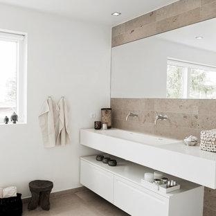 Design ideas for a contemporary bathroom in West Midlands with an integrated sink, flat-panel cabinets, white cabinets, beige tiles, stone tiles and white walls.