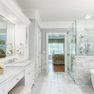 Immagine di una stanza da bagno padronale chic con ante con riquadro incassato, ante bianche, vasca freestanding, doccia ad angolo, piastrelle grigie, pareti grigie, lavabo sottopiano, pavimento grigio e porta doccia a battente