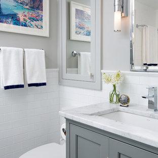 Immagine di una stanza da bagno classica con lavabo sottopiano, ante con riquadro incassato, ante grigie, piastrelle bianche, piastrelle diamantate e pareti grigie