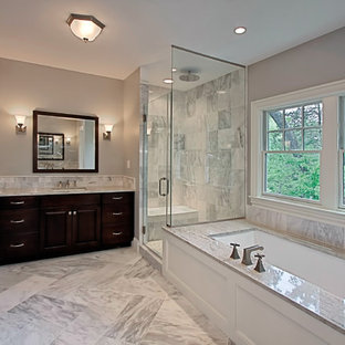 Mid-sized elegant gray tile and marble tile marble floor and gray floor corner shower photo in DC Metro with gray walls, raised-panel cabinets, dark wood cabinets, an undermount tub, an undermount sink, marble countertops and a hinged shower door