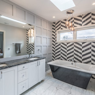 Example of a mid-sized transitional master black and white tile marble floor, white floor, double-sink and wall paneling freestanding bathtub design in Chicago with white cabinets, a one-piece toilet, gray walls, a drop-in sink and a freestanding vanity
