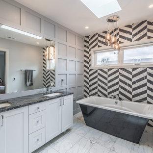 Modelo de cuarto de baño principal y panelado, tradicional renovado, de tamaño medio, panelado, con puertas de armario blancas, bañera exenta, sanitario de una pieza, baldosas y/o azulejos blancas y negros, paredes grises, suelo de mármol, lavabo encastrado, suelo blanco y panelado