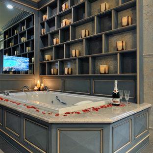 ニューヨークのトラディショナルスタイルのおしゃれな浴室 (レイズドパネル扉のキャビネット、グレーのキャビネット、ドロップイン型浴槽) の写真