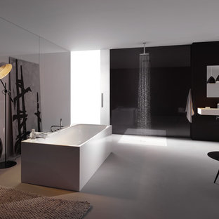 Design ideas for a large contemporary family bathroom in London with a wall-mounted sink, a freestanding bath, a walk-in shower, grey tiles and black walls.