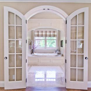 Diseño de cuarto de baño principal, tradicional, de tamaño medio, con bañera encastrada, baldosas y/o azulejos blancos y paredes beige