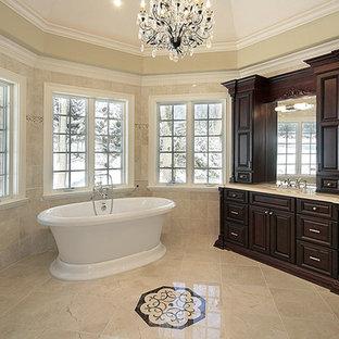 Foto di una grande stanza da bagno padronale classica con ante con bugna sagomata, ante in legno bruno, vasca freestanding, doccia alcova, WC a due pezzi, pareti beige, pavimento in marmo, lavabo sottopiano e top in pietra calcarea