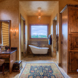 Inspiration for a large mediterranean ensuite bathroom in Austin with freestanding cabinets, medium wood cabinets, granite worktops, a claw-foot bath, a walk-in shower, brown tiles, beige tiles, stone tiles, travertine flooring, beige walls and brown floors.