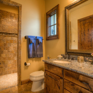Bathroom - mid-sized mediterranean 3/4 brown tile and stone tile travertine floor and brown floor bathroom idea in Austin with an undermount sink, raised-panel cabinets, medium tone wood cabinets, granite countertops, a two-piece toilet and beige walls