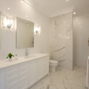 Design ideas for a large beach style master bathroom in Adelaide with shaker cabinets, white cabinets, a one-piece toilet, multi-coloured tile, stone tile, white walls, ceramic floors, an undermount sink, solid surface benchtops and a curbless shower.