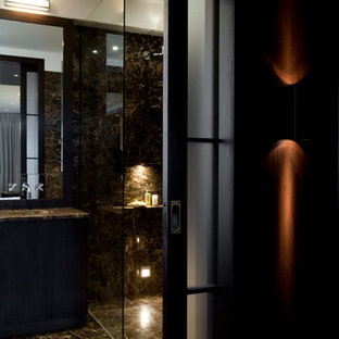 Photo of a medium sized contemporary ensuite bathroom in London with flat-panel cabinets, dark wood cabinets, a built-in bath, a walk-in shower, a wall mounted toilet, brown tiles, stone slabs, brown walls, marble flooring, a built-in sink, marble worktops, brown floors, an open shower and brown worktops.
