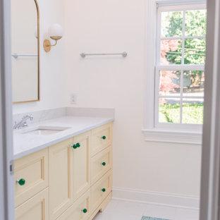 Modelo de cuarto de baño infantil, clásico, de tamaño medio, con armarios estilo shaker, puertas de armario amarillas, ducha empotrada, paredes blancas, lavabo bajoencimera, suelo multicolor, ducha con puerta corredera y encimeras blancas