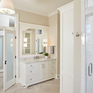 Foto de cuarto de baño principal, campestre, con armarios con paneles con relieve, puertas de armario blancas, ducha esquinera, paredes beige, suelo de bambú, encimera de cuarzo compacto, suelo marrón y ducha con puerta con bisagras