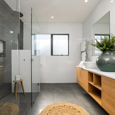 Trendy master gray tile gray floor bathroom photo in Sydney with flat-panel cabinets, brown cabinets, white walls, a vessel sink and white countertops