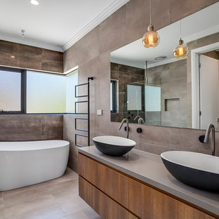 This is an example of a contemporary master bathroom in Sydney with flat-panel cabinets, brown cabinets, a freestanding tub, brown tile, gray tile, grey walls, a vessel sink, grey floor and grey benchtops.