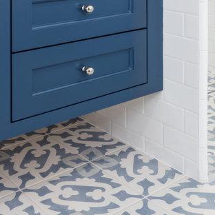 Inspiration för ett mellanstort lantligt vit vitt badrum med dusch, med luckor med profilerade fronter, blå skåp, en hörndusch, en toalettstol med hel cisternkåpa, vit kakel, keramikplattor, vita väggar, klinkergolv i keramik, ett undermonterad handfat, bänkskiva i kvarts, blått golv och dusch med gångjärnsdörr