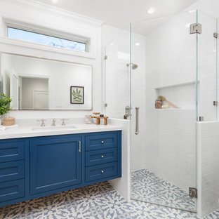 Corner shower - mid-sized country 3/4 white tile and ceramic tile ceramic tile and blue floor corner shower idea in San Francisco with blue cabinets, white walls, an undermount sink, quartz countertops, a hinged shower door, white countertops, recessed-panel cabinets and a two-piece toilet