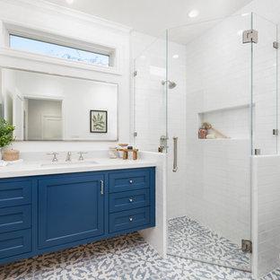 Ejemplo de cuarto de baño con ducha, de estilo de casa de campo, de tamaño medio, con puertas de armario azules, ducha esquinera, baldosas y/o azulejos blancos, baldosas y/o azulejos de cerámica, paredes blancas, suelo de baldosas de cerámica, lavabo bajoencimera, encimera de cuarzo compacto, suelo azul, ducha con puerta con bisagras, encimeras blancas, armarios con paneles empotrados y sanitario de dos piezas