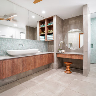 Design ideas for a beach style bathroom in Darwin with flat-panel cabinets, medium wood cabinets, blue tile, multi-coloured walls, a vessel sink and grey floor.