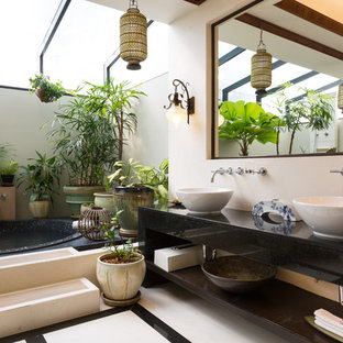 Inspiration for a tropical master bathroom in Los Angeles with a vessel sink, open cabinets, a drop-in tub and beige walls.