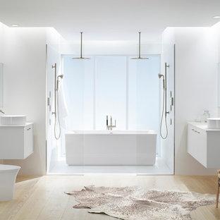 Imagen de cuarto de baño principal, minimalista, de tamaño medio, con armarios con paneles lisos, puertas de armario blancas, bañera exenta, ducha doble, sanitario de una pieza, paredes blancas, suelo de madera clara, lavabo sobreencimera y encimera de acrílico