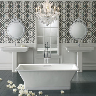 Mid-sized transitional master painted wood floor and gray floor freestanding bathtub photo in Other with a one-piece toilet, white walls and a pedestal sink